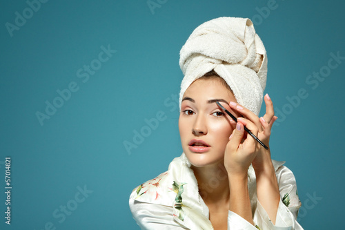 young attractive woman correcting eyebrow over blue background