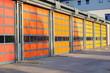 Leinwandbild Motiv Rote, gelbe und orange Garagentore eines Feuerwehrhauses