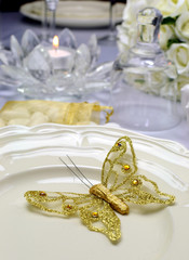 Wedding dining table setting with gold butterfly on plate