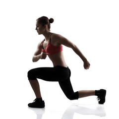sport young athletic woman doing lunge, silhouette studio shot o