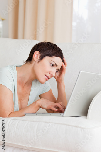 Tired young woman using a laptop