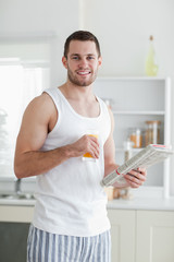 Portrait of a smiling man drinking orange juice while reading th