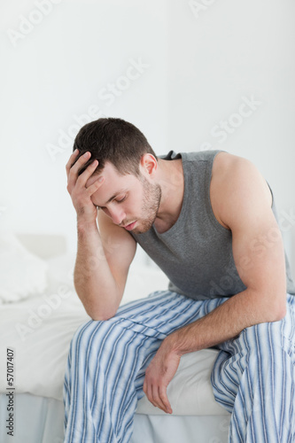 Portrait of an exhausted man sitting on his bed