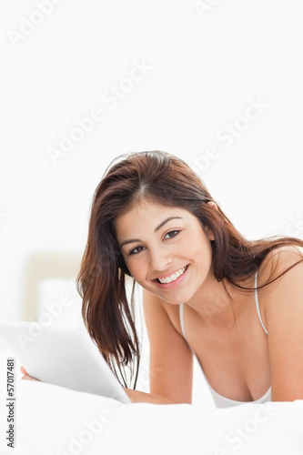 Woman smiling and looking forward and holding a tablet