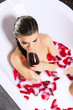 Attractive naked girl enjoy a glass of wine in bath with milk