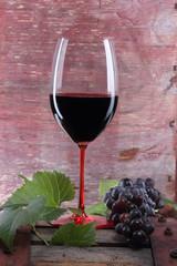 bicchiere di vino rosso con uva su tino