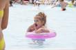 Замерзшая девочка стоит с кругом в бассейне