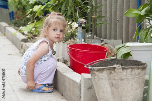 Девочка сидит в саду с ведром у поливочного крана