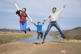 happy family jumping on the mountain