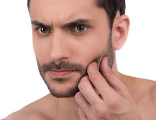 Close up of man's unshaven face. Man touches his skin