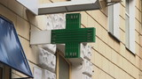 Pharmacy, drug store green neon cross lighted at daytime, city