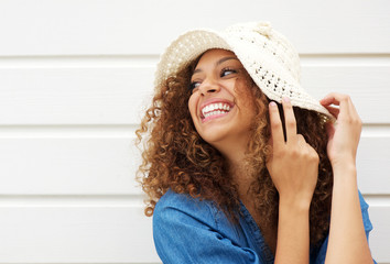 Beautiful young woman laughing and wearing summer hat