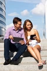 Девушка с парнем сидят на лестнице с планшетом