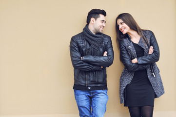 Young happy cheerful couple standing near a wall and looking to