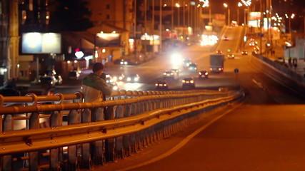 Night city cameraman shooting traffic on bridge road junction