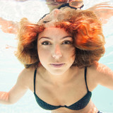 Beautiful woman portrait underwater in swimming pool.