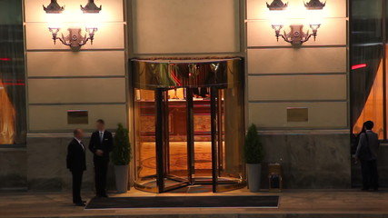 Hotel entrance night time lapse, visitors guests come in out