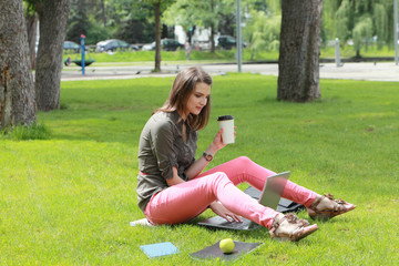 Young Woman with Computer in an Urban Park
