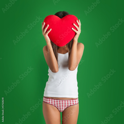 Portrait of young woman hiding behind red heart against green ba