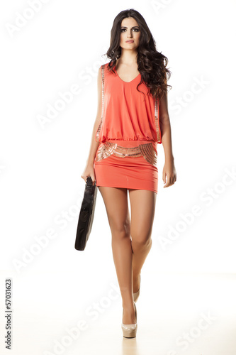 pretty girl in orange dress and laptop bag walking towards you