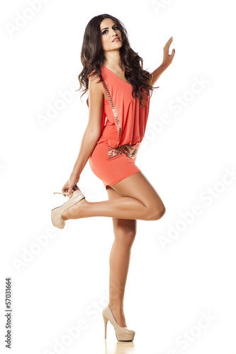pretty girl in orange dress putting on her high-heeled shoes