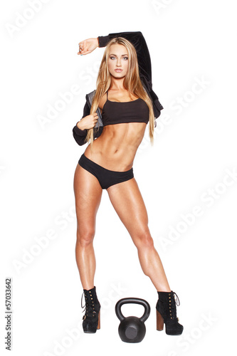 Sexy fitness model posing with kettlebell