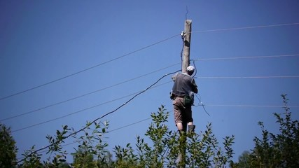 Electrician attaches to an electric pole aluminum wire.