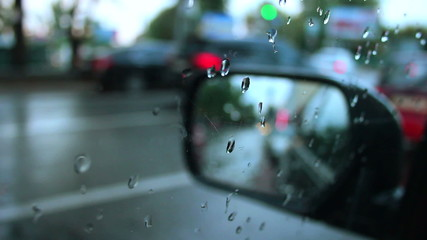 Side rear view mirror rainy weather, wet cars road city