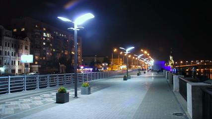 Night city quay, people walking, cars driving, street lights on