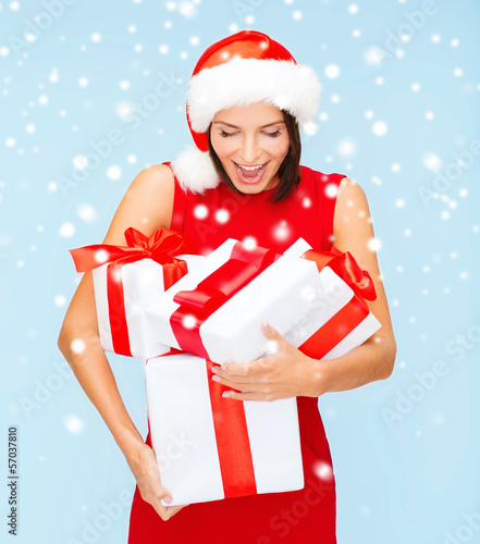 surprised woman in santa hat with many gift boxes