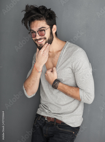 sexy fashion man with beard dressed casual smiling against wall