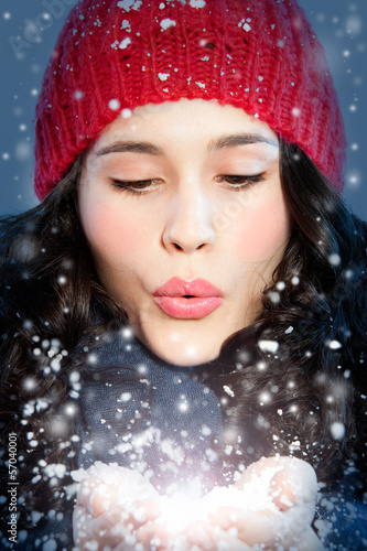 Christmas girl blowing snow in hands