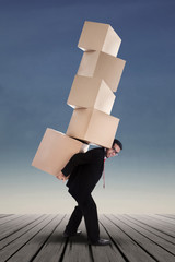 Businessman lifting boxes vertical