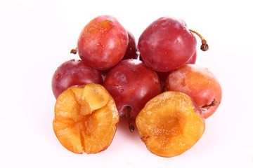Plums on white background - one cut in half