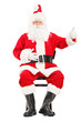 Happy Santa claus sitting on a chair and giving a thumb up