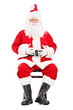 Happy Santa claus sitting on a wooden chair