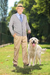 Senior man and his Labrador retriever dog in a park