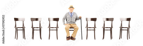 Relaxed senior gentleman sitting on a wooden chair