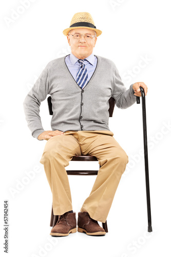 Relaxed senior man sitting on a chair and looking at camera