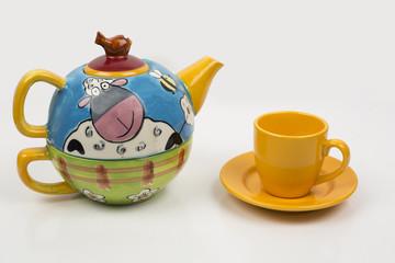 Taza de té y tetera de cerámica decorada con motivos infantiles