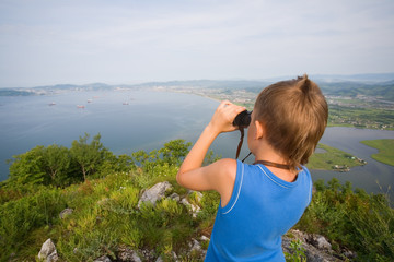 Boy looking through binoculars from the top of the mountain