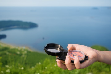 Boy hand holding a compass on the background of a seascape