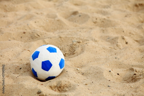 soccer ball on sandy beach background