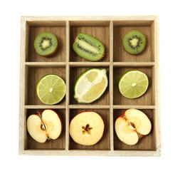 Sliced fruit in wooden box isolated on white