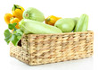 Raw yellow and green zucchini in wicker crate, isolated on
