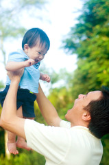 Asian father playing with baby boy