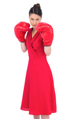 Elegant brunette in red dress wearing boxing gloves