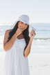 Happy brunette in white sunhat looking at camera