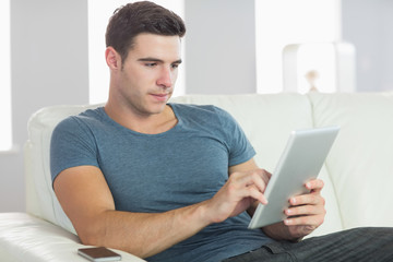 Content handsome man relaxing on couch using tablet