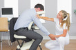 Masseuse treating clients arm in massage chair